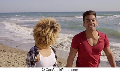 Young Couple Walking On The Beach - Young mixed-race...