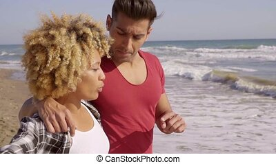 Young Mixed-Race Couple Standing On The Beach - Young...