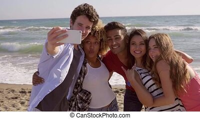 Funny Pictures On The Beach - Group of young people makes a...