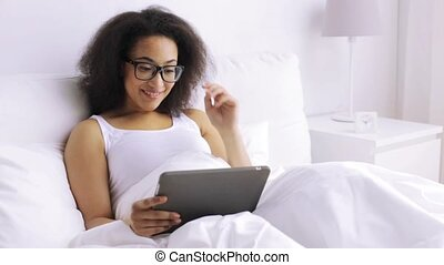 african woman with tablet pc in bed at home - rest,...