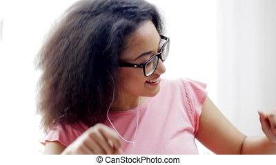 african woman with earphones listening to music