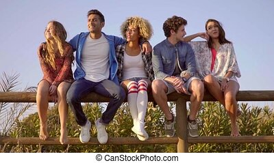 Young People Sitting On Wooden Fence - Group of young people...