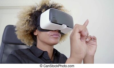 Young woman wearing virtual reality glasses raising her...