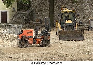 Two construction vehicles in building land