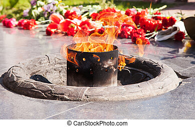 an eternal flame burns at the monument on spring day closeup