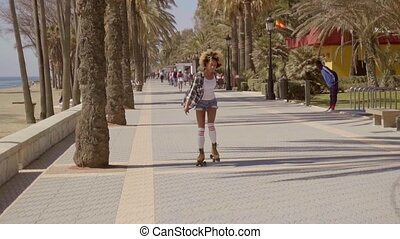 Woman Riding On Vintage Roller Skates. - Young woman dressed...