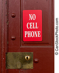 Red sign for no cell phone usage - Sign on red painted door...