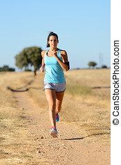 Woman running cross trail in country path