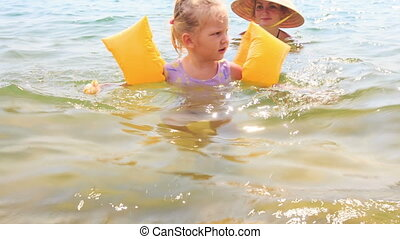 Closeup Little Girl in Safety Armbands Goes out of Sea -...