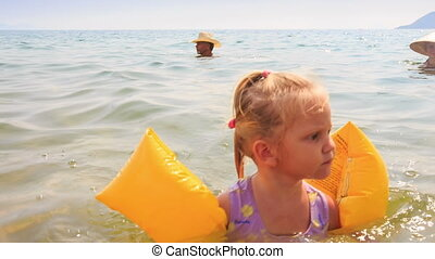 Closeup Little Girl in Armbands Goes out of Sea to Beach -...