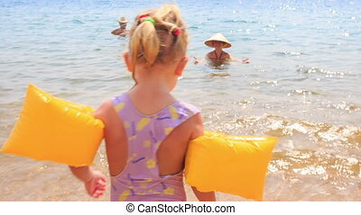 Closeup Little Girl in Safety Armbands Goes to Mother in Sea...