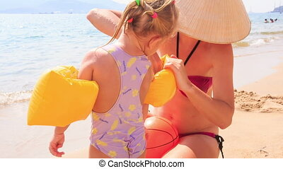 Mother Takes off Armbands from Little Girl on Sand Beach -...