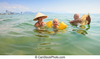 Little Girl in Armbands Swims from Mother to Grandpa in Sea...