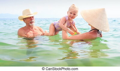 Old Man Mother Lift up Little Daughter Play in Azure Sea -...