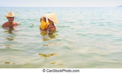 Little Girl in Armbands Swims with Mother Grandpa in Azure Sea
