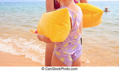 Mother Puts Safety Armbands on Daughter on Sand Beach -...