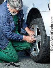 mechanic changing a wheel of a modern car (color toned...