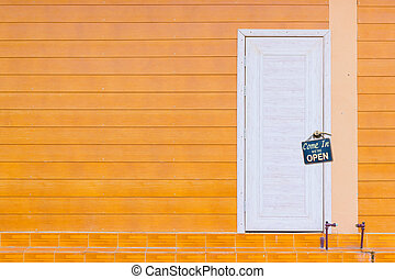 white wooden door and the orange wall with old rusty...