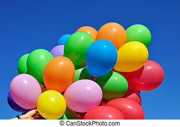 multicolored balloons in the human hand