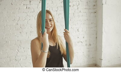 Anti-gravity Yoga, Happy Woman smiling in Sport Class.