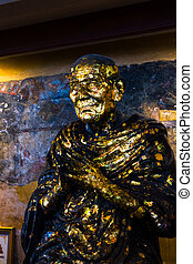 Statue covered in gold leaf at Temple of the Reclining Buddha Wat Pho, Bangkok, Thailand.