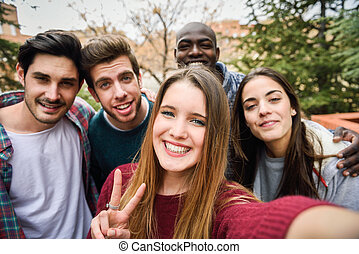 Multiracial group of friends taking selfie in a urban park