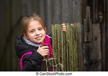 Little cute girl near the fence