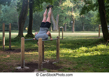 Hand Stand On Parallel Bars In Outdoor Park - Athlete...