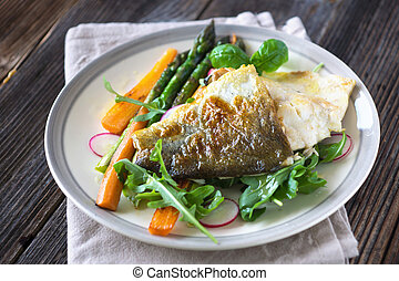 Fish fillet with vegetables on wooden background