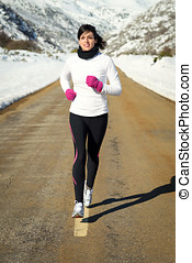 Woman running in winter on road