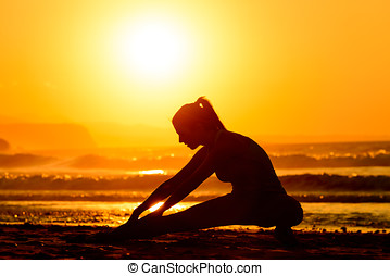 Stretching exercises on beach at sunset - Woman stretching...