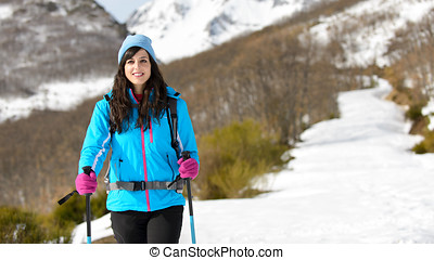 Woman winter hiking in snowy track