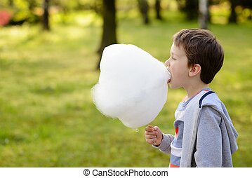 7 years boy eating candy floss in the park - Child - 7 years...