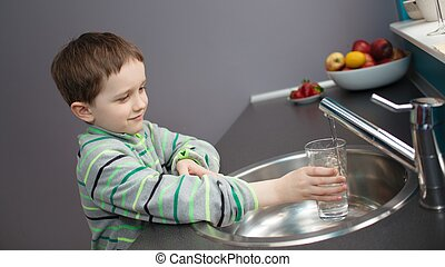 boy pouring tap water into a glass - Child - 7 year old boy...