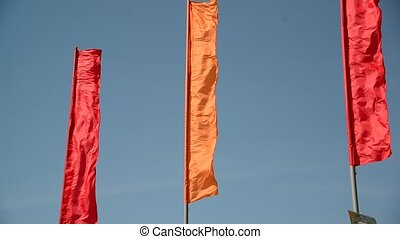 red and orange flags swaying in  wind
