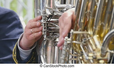 Musicians playing on the golden tubas - Close-up of tuba...