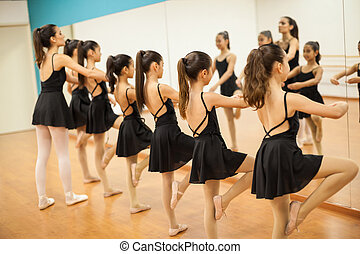 Group of girls and teacher in a dance academy - Row of many...