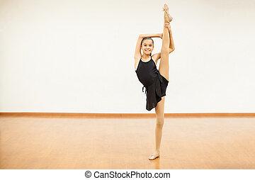 Cute girl doing a leg split in dance class - Full length...