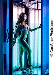 Pretty woman posing while tans in modern solarium - Pretty...