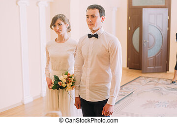 Smiling happy bride with wedding bouquet and groom standing...
