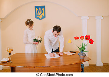 Handsome smiling groom signing wedding certificate at...