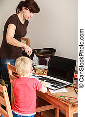 Little boy with laptop and mother cooking - Technology and...