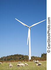 Sheep grazing at the foot of a wind turbine   against a sunny blue sky with copy space