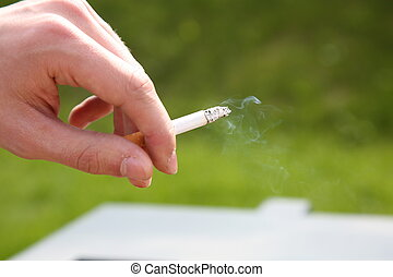 hand with a smoking cigarette