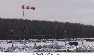 Wind cone on a runway - White and red wind cone waving on a...