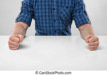 Closeup masculine fists clenched on the table Anger sign...