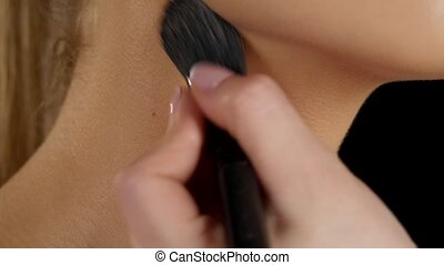 Foundation. Applying foundation on the neck. Closeup -...