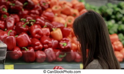Young woman chooses paprika on store shelves - Young...