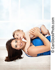 Joyful mother play with son - Cheerful joyful mother playing...