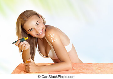 Happy woman applying sunscreen - Portrait of a beautiful...